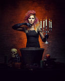 Jonge en mooie heks die hekserij in de kerker maken stock foto