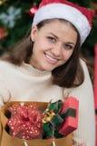 Jonge en mooie Kaukasische vrouw in rode hoed en holdingszak o stock afbeeldingen