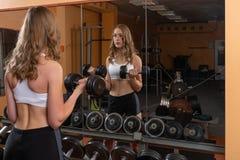 Jonge en mooie vrouw die in de spiegel kijken en met domoren in gymnastiek uitwerken - Beeld royalty-vrije stock afbeeldingen