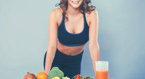 Jonge en mooie vrouw die zich dichtbij bureau met groenten bevinden Royalty-vrije Stock Foto's