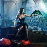 Jonge en sexy vrouw, beeld van heksen in een begraafplaatszitting op dekseldoodskist stock afbeeldingen