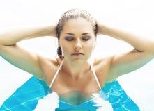 Jonge en sportieve vrouw in zwempak Meisje het ontspannen in een pool bij de zomer royalty-vrije stock afbeelding