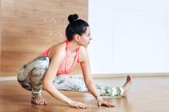 Jonge en vrouw die alvorens bij een yoga uit te werken uitrekken zich opwarmen Stock Afbeeldingen