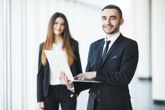 Jonge en zekere zakenman met laptop die zich voor bedrijfsvrouw bevinden Royalty-vrije Stock Afbeeldingen