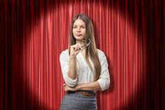 Jonge ernstige donkerbruine bedrijfsvrouw die met glazen op de rode achtergrond van stadiumgordijnen denken royalty-vrije stock foto