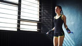 Jonge ernstige vrouwelijke bokser in het verpakte handen opwarmen, die op touwtjespringen in gymnastiek vrije ruimte springen stock fotografie