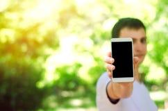 Jonge Europese kerel die een smartphone in zijn hand houden telefoonafhankelijkheid, sociale netwerken Het werk aangaande Interne royalty-vrije stock afbeeldingen