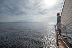 Jonge Europese mens die zich bij op zee rand van jacht bevinden die eruit zien Stock Afbeelding
