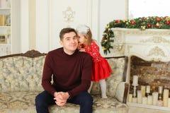 Jonge Europese vaderzitting met weinig dochter op bank dichtbij verfraaid open haard stock afbeelding