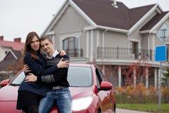 Jonge familie dichtbij rode auto op achtergrondhuis Stock Fotografie