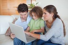 Jonge familie die een notitieboekje gebruikt Stock Foto