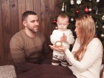 Jonge familie die Kerstmisboom verfraait Stock Afbeelding