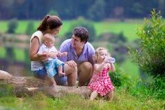Jonge familie die met jonge geitjes bij een meer wandelen royalty-vrije stock afbeelding
