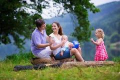 Jonge familie die met jonge geitjes bij een meer wandelen royalty-vrije stock afbeeldingen