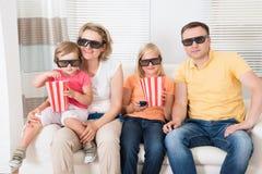 Jonge familie die op 3d TV letten Stock Afbeeldingen