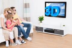 Jonge familie die op 3d TV letten Stock Fotografie