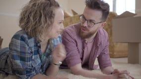 Jonge familie die op pluizig tapijt dicht omhoog met dozen in de achtergrond liggen Man die sleutel tonen aan vrouw, zich uit uit stock video