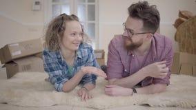 Jonge familie die op pluizig tapijt dicht omhoog met dozen in de achtergrond liggen De mens geeft sleutels aan zijn vrouw, mensen stock video