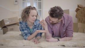 Jonge familie die op pluizig tapijt dicht omhoog met dozen in de achtergrond liggen Mensen verbergende sleutel van zijn vrouw ter stock footage