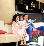 Jonge familie die op TV letten Royalty-vrije Stock Foto's