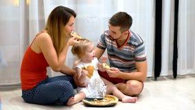 Jonge familie die pizzazitting op de vloer eten stock footage