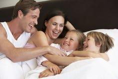 Jonge Familie die Pret in Bed hebben stock foto's