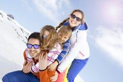 Jonge familie die pret in de sneeuw hebben stock afbeelding