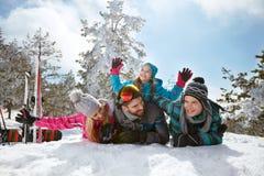 Jonge familie die pret hebben en in sneeuw op de wintervakantie spelen Royalty-vrije Stock Foto's