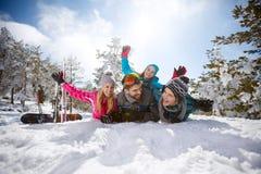 Jonge familie die pret op sneeuw in berg hebben royalty-vrije stock afbeelding