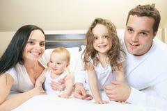 Jonge familie die samen in het bed van de ouder rusten Stock Fotografie