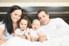 Jonge familie die samen in het bed van de ouder rusten Stock Foto