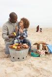 Jonge Familie die van Barbecue op Strand geniet stock foto's