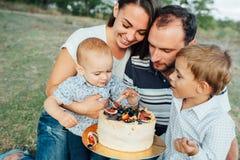 Jonge Familie die van Cake in Park genieten Stock Afbeelding