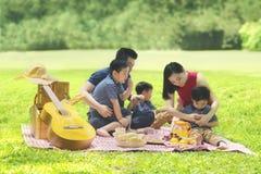 Jonge familie die van hun vakantie in het park genieten royalty-vrije stock foto's