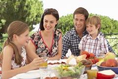 Jonge Familie die van Openluchtmaaltijd samen genieten royalty-vrije stock foto