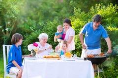Jonge familie die vlees voor lunch met grootmoeder roosteren stock foto