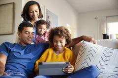 Jonge familie het besteden tijd die samen een tabletcomputer in hun woonkamer, vooraanzicht met behulp van stock fotografie