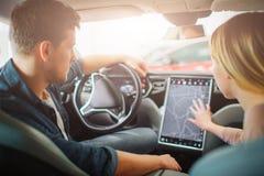 Jonge familie het kopen eerste elektrische auto in de toonzaal Aantrekkelijk paar die een manier op elektronisch dashboard binnen royalty-vrije stock afbeeldingen