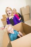 Jonge Familie in het Lege Zaal Spelen met het Bewegen van Dozen stock afbeelding