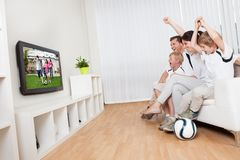 Jonge familie het letten op voetbal royalty-vrije stock fotografie
