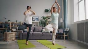 Jonge familie het praktizeren yoga in flat het in evenwicht brengen op één been op matten stock footage