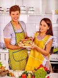 Jonge familie kokende pizza bij keuken Stock Afbeelding