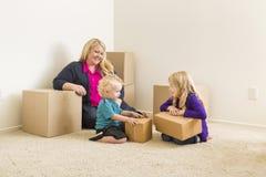 Jonge Familie in Lege Zaal met het Bewegen van Dozen Stock Fotografie