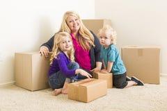 Jonge Familie in Lege Zaal met het Bewegen van Dozen Stock Foto