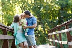 Jonge familie met baby in de zomerpark Stock Foto's