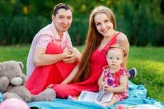 Jonge familie met dochter en boekzitting op plaid stock afbeelding
