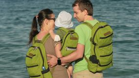 Jonge familie met een baby die het overzees en het koesteren bekijken Iedereen heeft rugzakken op hun ruggen Strand en mensen stock footage