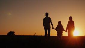 Jonge familie met een kind die de zonsondergang op het gebied bewonderen, die handen houden royalty-vrije stock foto