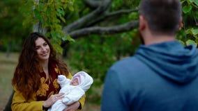 Jonge familie met pasgeboren baby in het park stock videobeelden