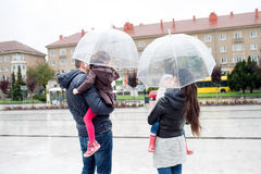 Jonge familie met twee dochters onder de paraplu's, stad Stock Afbeeldingen